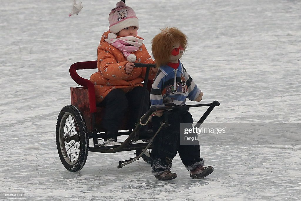A little girl drives a robot rickshaw on the frozen Houhai Lake during severe pollution on February 3, 2013 in Beijing, China. Houhai Lake is a popular place for winter sport and entertainment in Beijing.