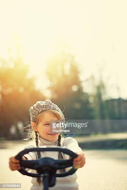 Little girl driving gokart in the park