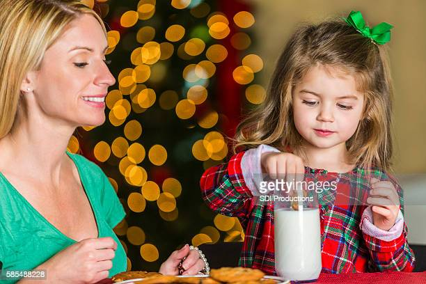 Little girl dunks a cookie in milk on Christmas Eve