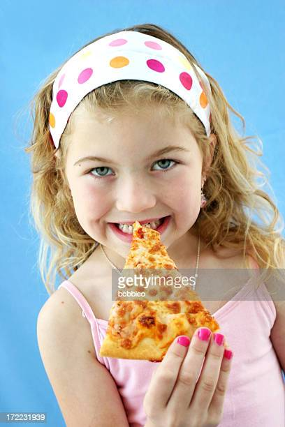 A little girl eating a slice of pizza