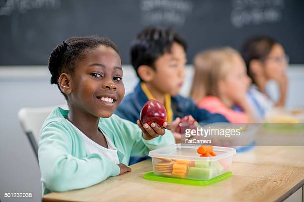 Little Girl Eating an Apple in Class