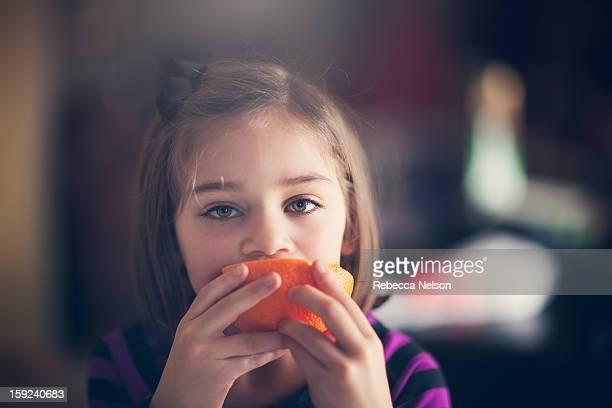 Little Girl Eating an Orange