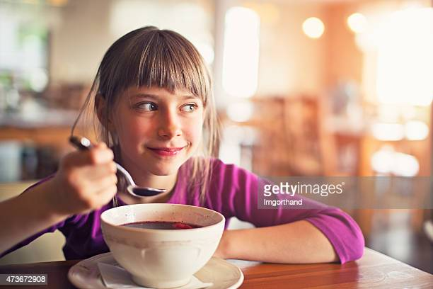 Little girl eating beetroot soup