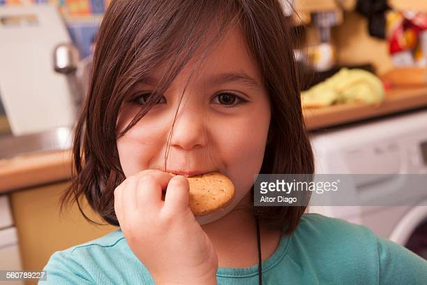 Little girl eating biscuit in the kitchen.