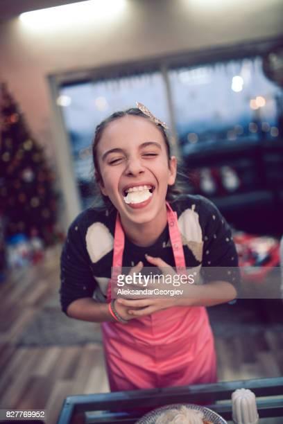 Kleine Mädchen essen Kuchen und lächelnd mit vollem Mund