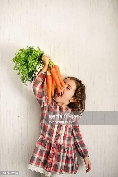 Little girl eating carrots