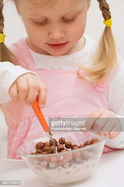 Little girl eating cereal with milk