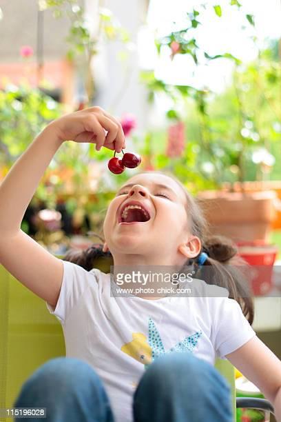 Little girl eating cherries