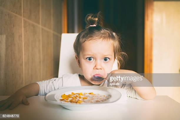 Little girl eating corn flakes