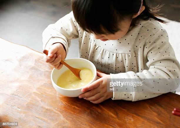 Little girl eating corn soup