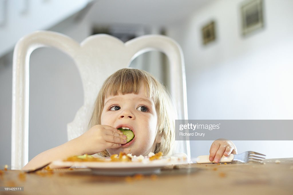 Little girl eating cucumber : Stock Photo