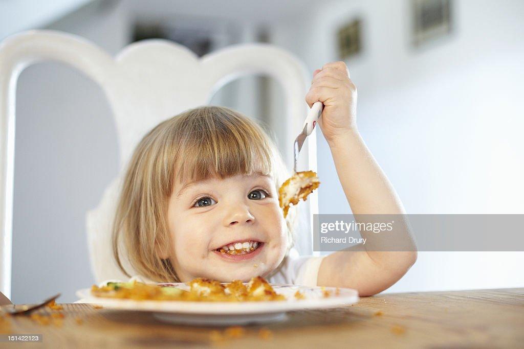 Little girl eating fish fingers : Stock Photo