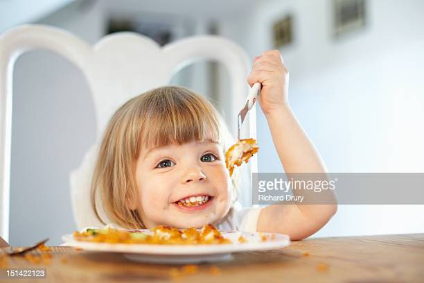 Little girl eating fish fingers