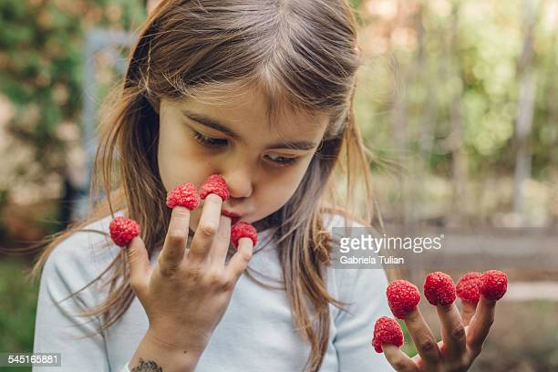 Little girl eating fresh raspberries