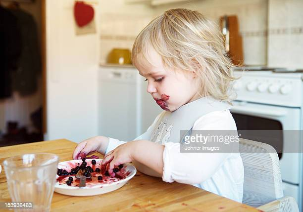 Little girl eating fruits in kitchen