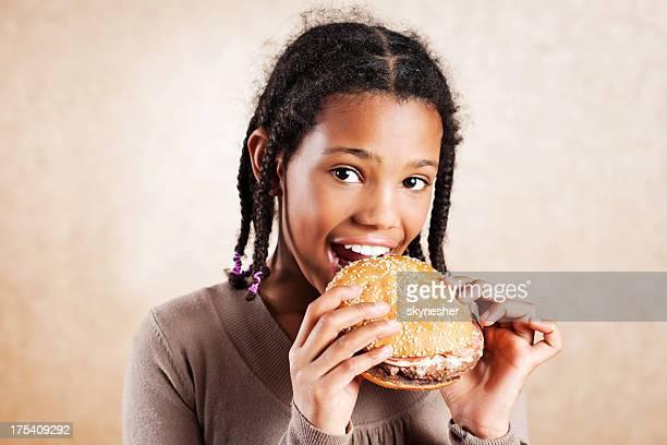 Kleine Mädchen Essen hamburger, genießen Sie fast food.
