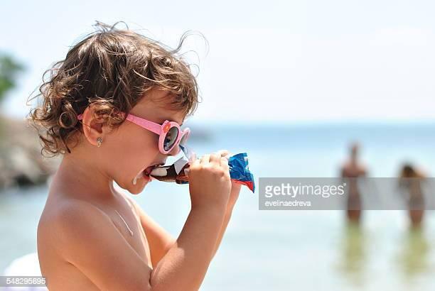 little girl eating ice cream on the beach of sea