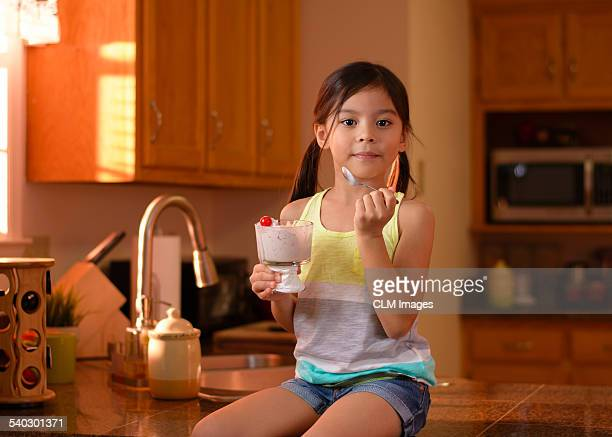 Little girl eating ice cream sitting, counter top.