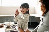 Little girl eating meal,smiling