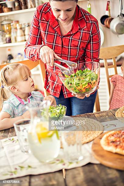 Little Girl Eating Pizza with Fresh Salad
