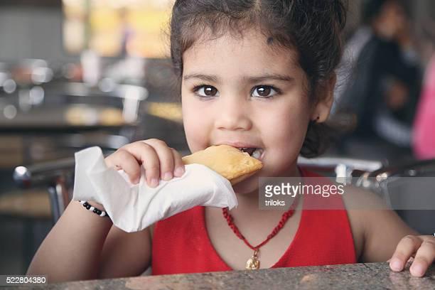 Little girl eating puff food