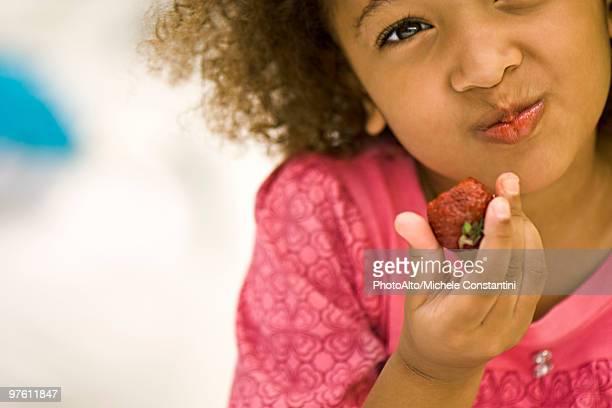 Little girl eating strawberry
