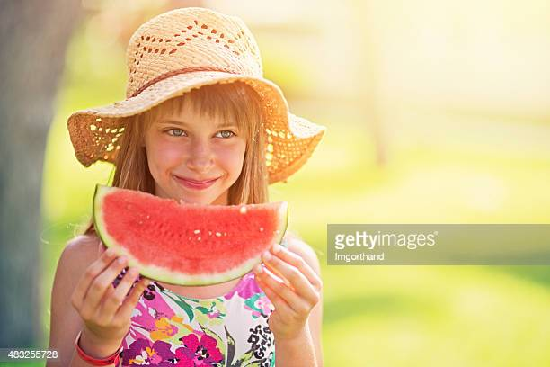 Little girl eating watermelon outdoors