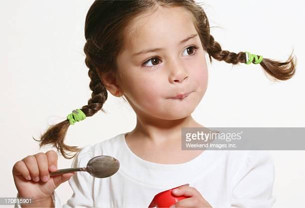 Kleines Mädchen isst yougurt