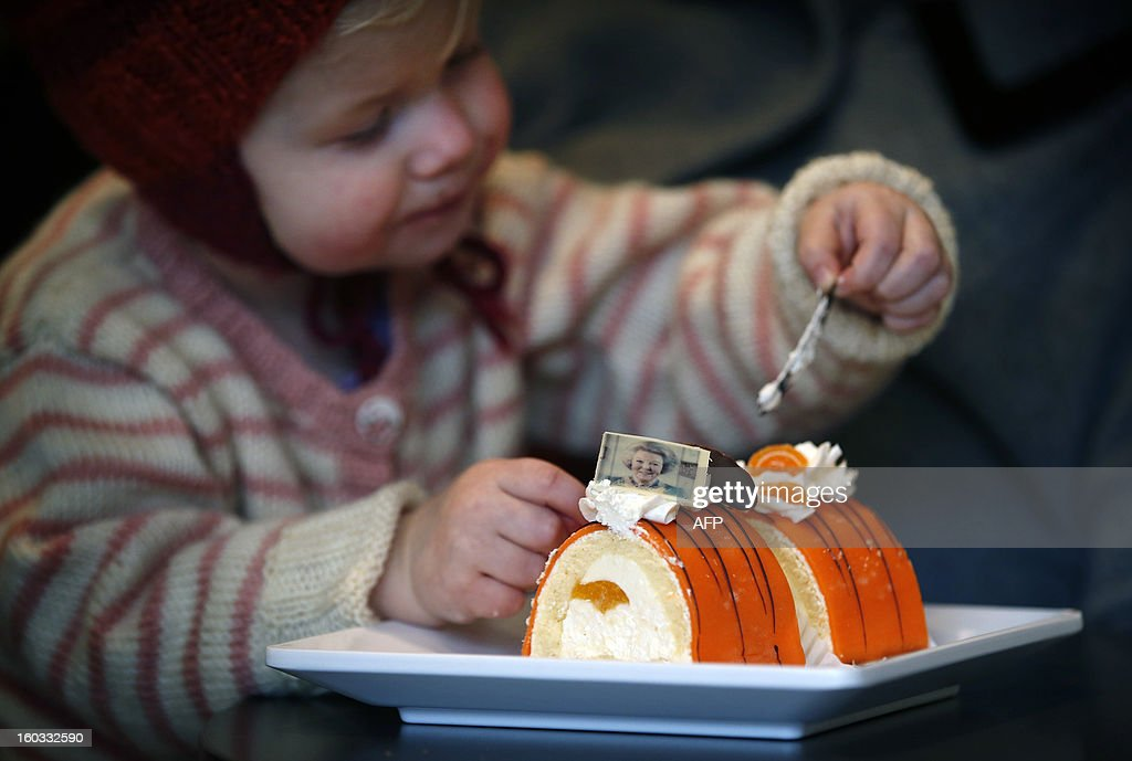 A little girl eats a special cake with a picture of Queen Beatrix on it in a bakery in Leeuwarden, The Netherlands, on January 29, 2013. The Queen announced yesterday her abdication. AFP PHOTO/ CATRINUS VAN DER VEEN netherlands out