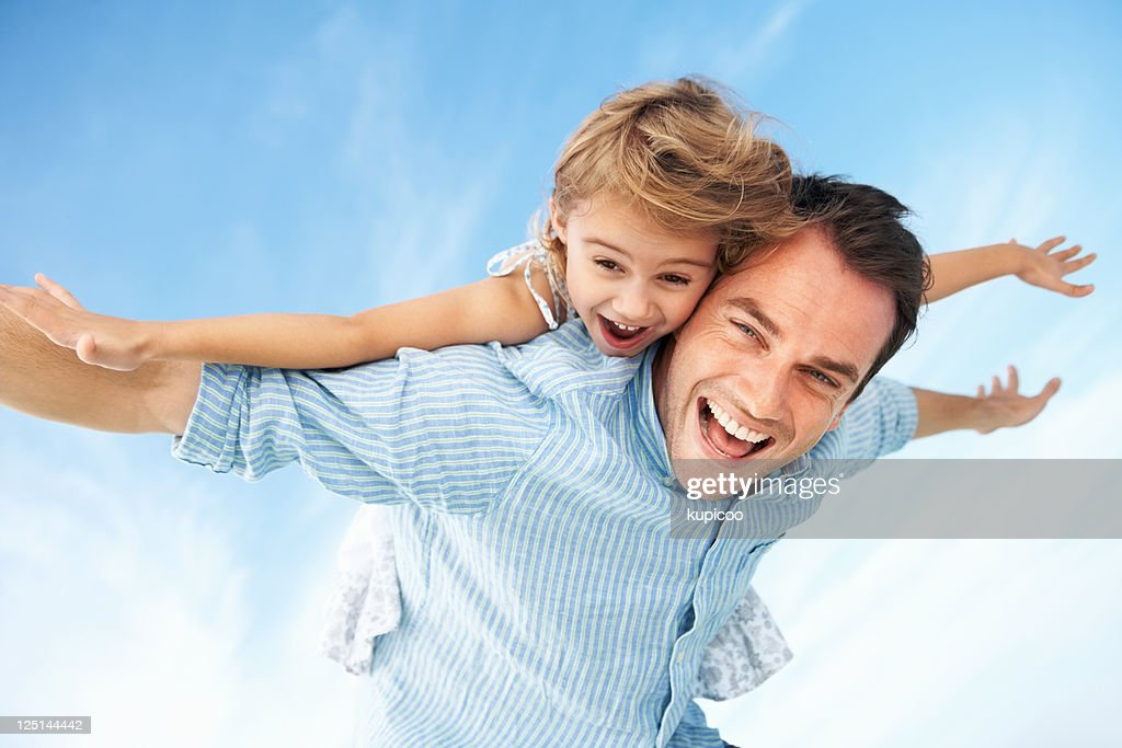 Little girl enjoying piggyback ride with father : Stock Photo