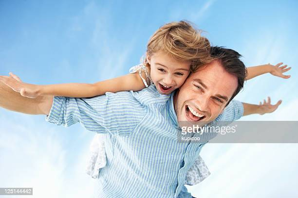 Little girl enjoying piggyback ride with father