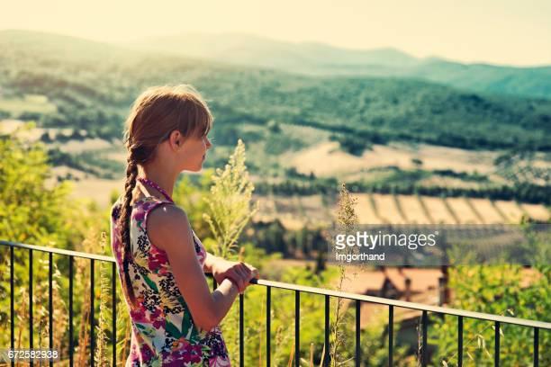 Little girl enjoying tuscany view from balcony