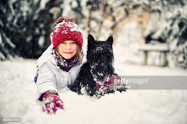 Bambina con il suo cane godendo inverno.