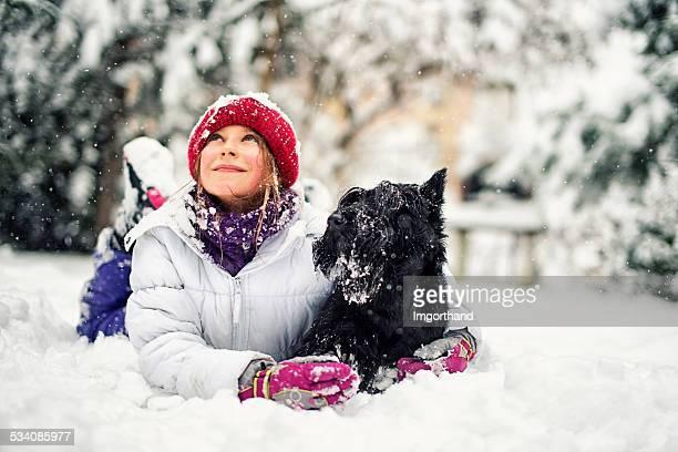 Kleines Mädchen mit Ihrem Hund Genießen Sie den winter.