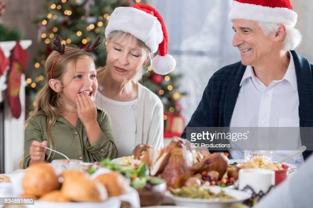 Meisje geniet kerstdiner met grootouders