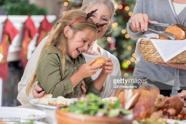 Meisje geniet van ontvangst van een broodje op kerstdiner