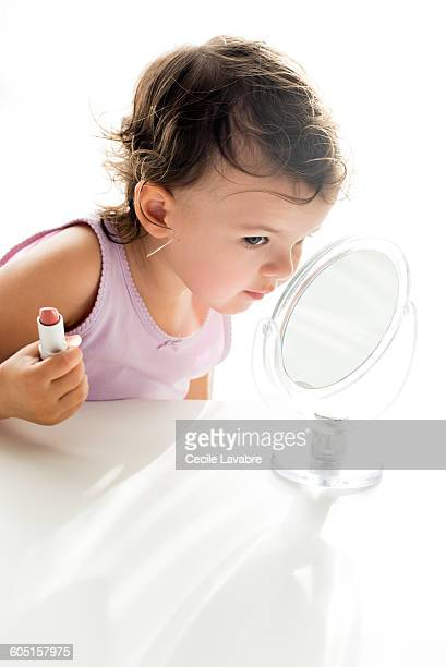 Little girl examining lipstick in the mirror