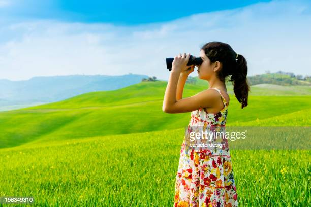 Little girl exploring with binoculars in Tuscany - Italy