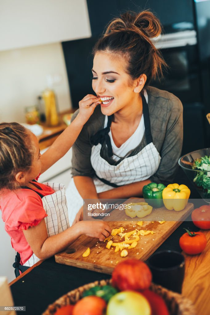Little girl feeding her mother : Stock Photo