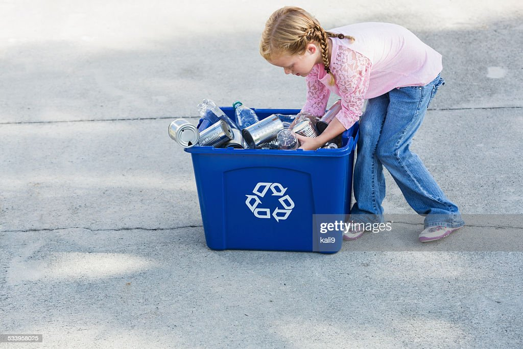 Little girl filling recycling bin with cans and bottles : Stock Photo