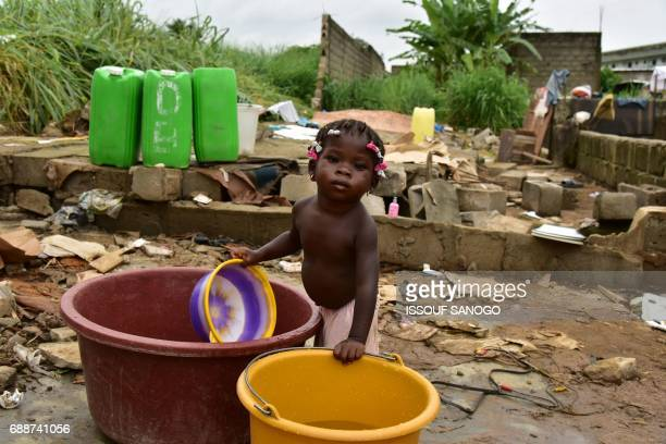 TOPSHOT A little girl fills a water bucket as residents of a shanty town in Abidjan sort through the remains of their homes on May 26 2017 in Abidjan...