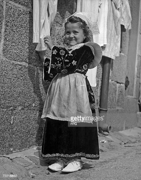 A little girl from Concarneau in Brittany takes down her parent's best linen in preparation for the Pardon of Ste Anne D'Auray circa 1930