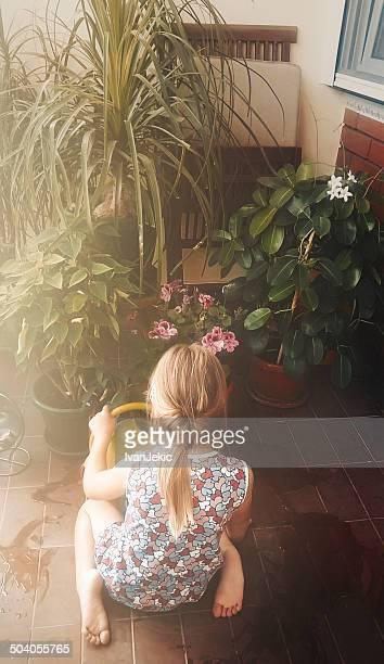 Little girl gardening her plants on balcony