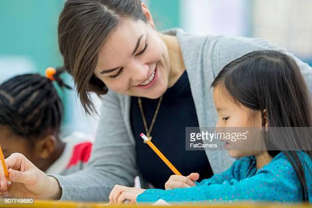Piccola bambina ottenere aiuto del suo insegnante
