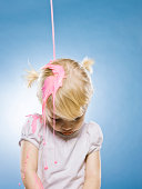 little girl getting pink paint poured on her head