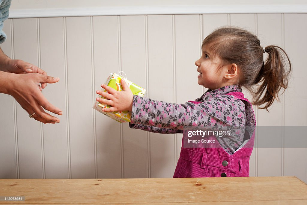 Little girl giving a gift to adult