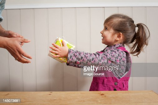 Little girl giving a gift to adult : Stock Photo