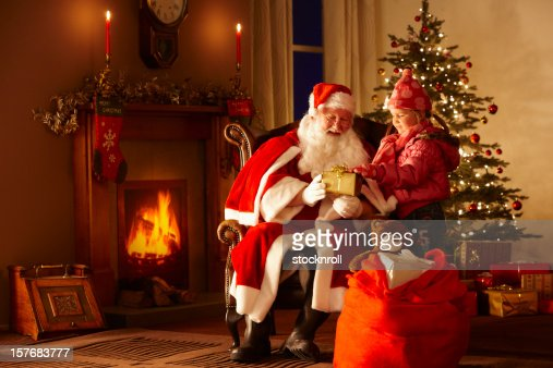 Little girl giving gift to Father Christmas in grotto