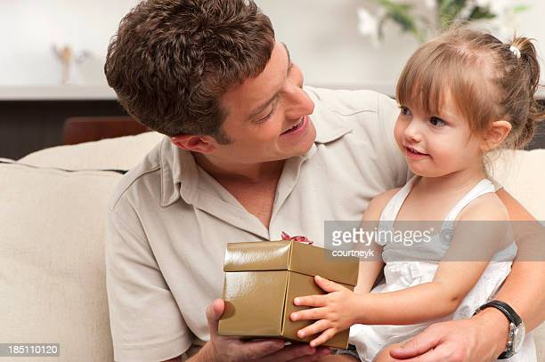 Little girl giving her father a gift