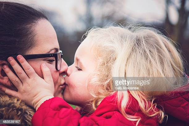 Little girl giving her Mummy a big kiss